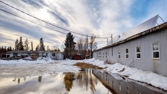 Sunlight hits a pool of melted snow and solar panels atop the Liidlii Kue First Nation's office in Fort Simpson on March 19, 2019