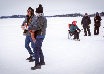 The Grapes of Wrath play in front of a family taking part in the NWT Family Fish Derby, on Prelude Lake, on April 6, 2019