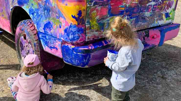 Children paint a police truck in Inuvik
