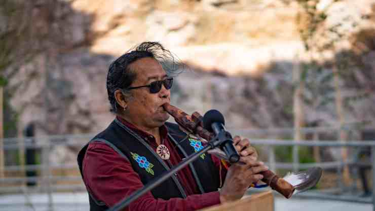 William Greenland plays a flute song at the grand opening of the Stanton Territorial Hospital in July 2019. Sarah Pruys/Cabin Radio