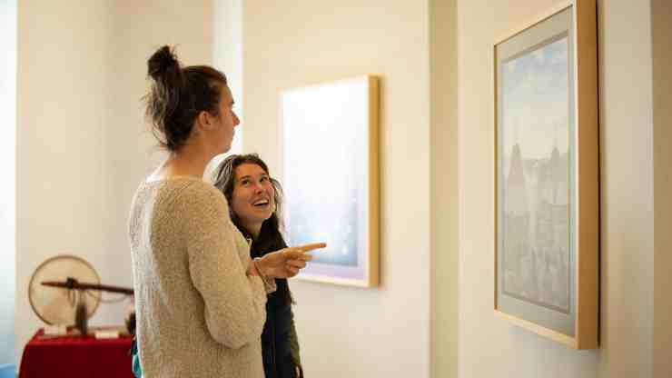 "Attendees chat about a painting by Behchokǫ̀'s Louis Angus Beaulieu called ""Circle of Wellness,"" at the opening of the Stanton Territorial Hospital. Sarah Pruys/Cabin Radio"