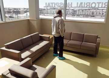A resident stands inside the second-floor lounge of the new Stanton Territorial Hospital in April 2019