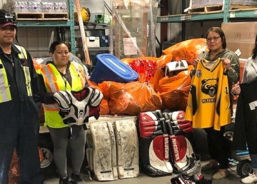 Air Tindi staff with hockey equipment donated by the North Delta Minor Hockey Association