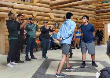 Edmonton Eskimos players watch Inuvik students performing Inuvialuit traditional games