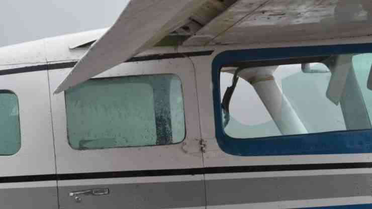An image shows the flaps blocking the emergency exit on the retrieved Cessna 206