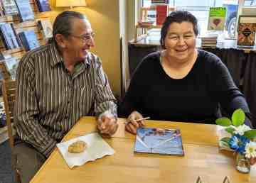 Henry and Eileen Beaver sign copies of their book, Sharing Our Truths, in Yellowknife in November 2019. Sarah Pruys/Cabin Radio
