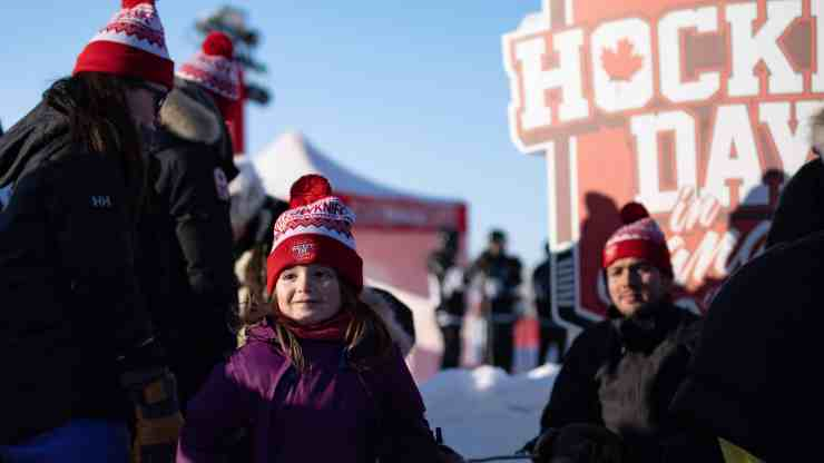 A child poses in front of the Hockey Day in Canada sign during the hockey festival in Yellowknife. Sarah Pruys/Cabin Radio