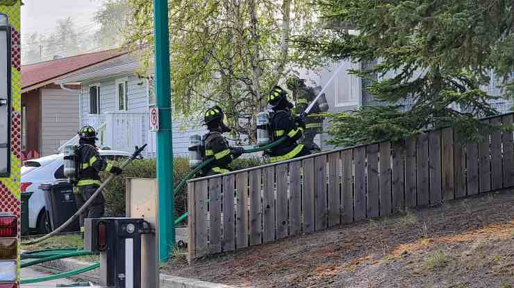 Firefighters prepare to attack a house fire on Yellowknife's 50A Avenue. Ollie Williams/Cabin Radio
