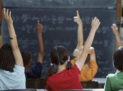 Rear view of class raising hands --- Image by © Royalty-Free/Corbis