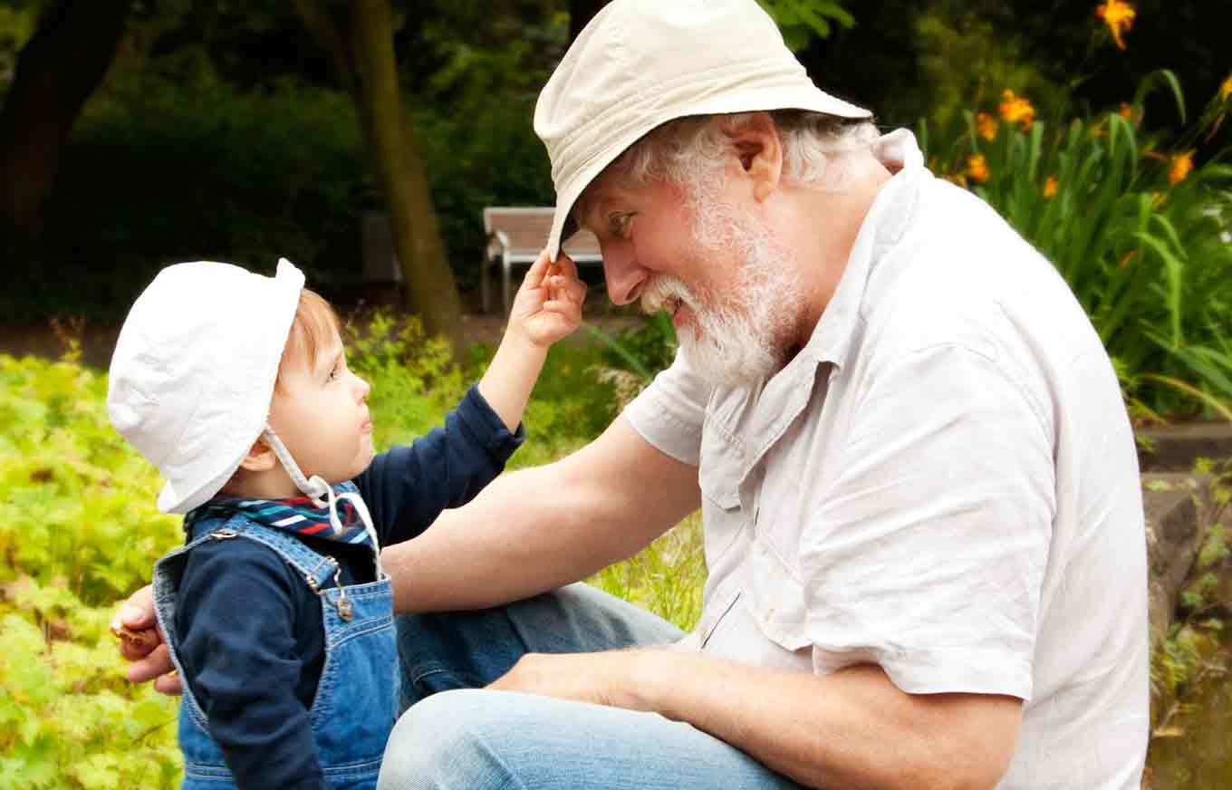 Child pulling down grandfather's hat