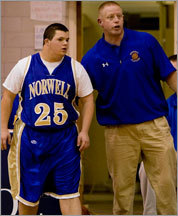 Norwell guard Andrew Lawson (left), who has Down syndrome, gets some coaching advice from coach John Willis before going into the game against Hanover Thursday.