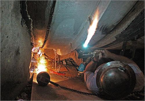 Tunnel workers weld the broken water main