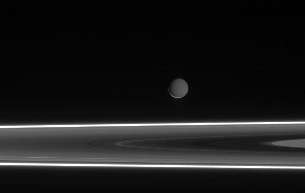 Encelado en la distancia, tras el sistema de anillos de Saturno
