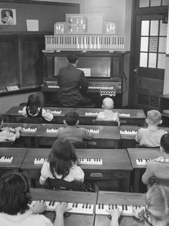 Black and white photograph of a classroom: seven children sit at keyboards; a male teacher in a suit plays a large keyboard and keys and notes on a staff light up above his head; to the left is a blackboard, and to the right is a door with nine panes of glass in the upper half; the middle pane is covered with a piece of paper drawn with a brick pattern