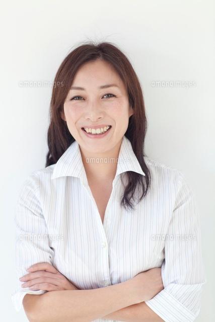 腕を組んで笑顔の中年女性[10373002344]  寫真素材・ストックフォト・畫像・イラスト素材 アマナイメージズ