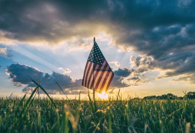 Sunset beyond the American Flag celebrating 4th of July Independence Day. Photo by Aaron Burden. http://aaronburden.com/, via https://www.goodfreephotos.com/holidays/4th-of-july-independence-day/sunset-beyond-the-american-flag-celebrating-4th-of-july-independence-day.jpg.php , public domain.