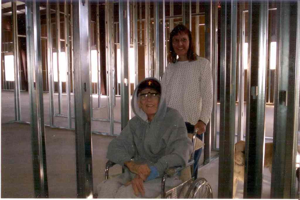 Mary Ann pushing Fr Rick Thomas in a wheelchair