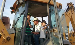 Children helping their grandfather in a tractor.
