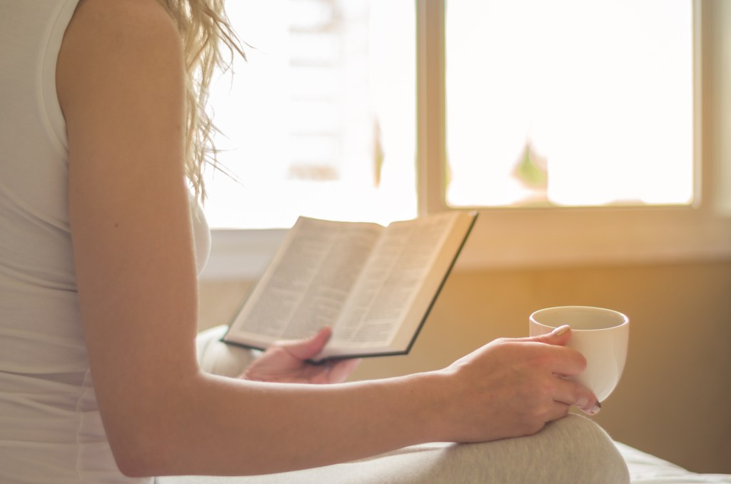 Woman reading book, drinking coffee in bed with solar rays in the window.