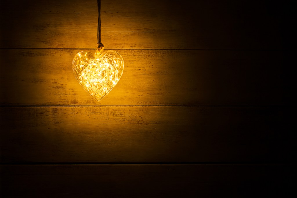 Hanging warm glowing orange heart on a wooden background