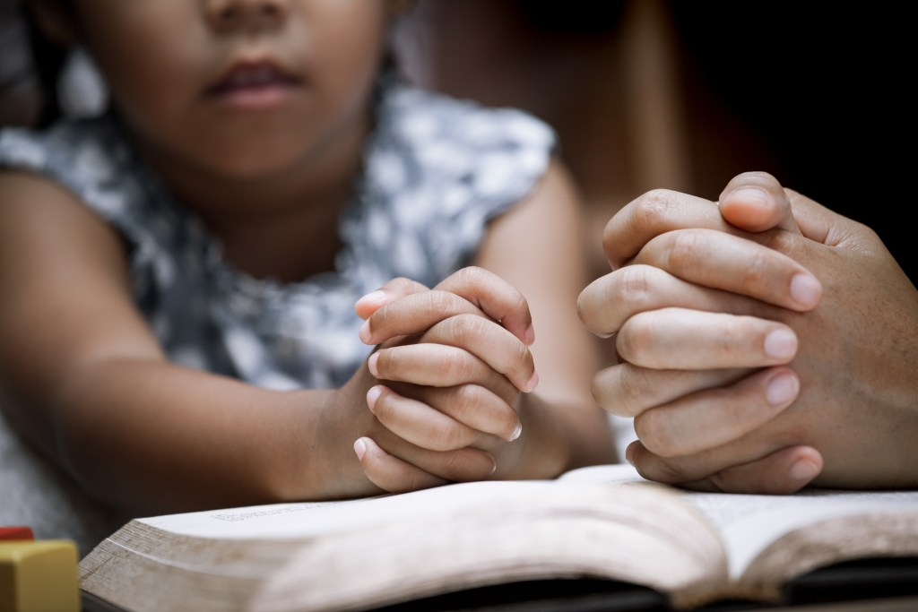 Mother and little girl hands folded in prayer on a Holy Bible together