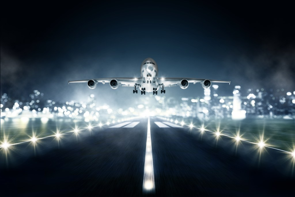 airplane landing at night on lighted runway