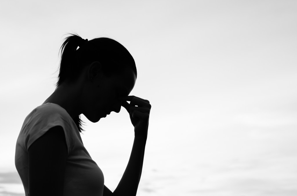 Silhouette of a tired and stressed woman.