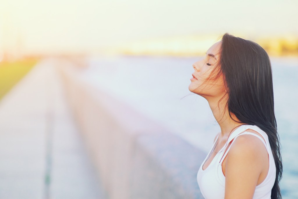 Side view profile portrait of a woman relaxing breathing fresh air outdoors. peace of mind,