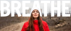 Beautiful young woman with long hair inhales fresh air with her eyes closed with big white word breathe in the background. Banner, freedom concept, the ability to breathe fresh air on the street