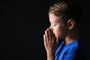 Portrait of praying boy on dark background