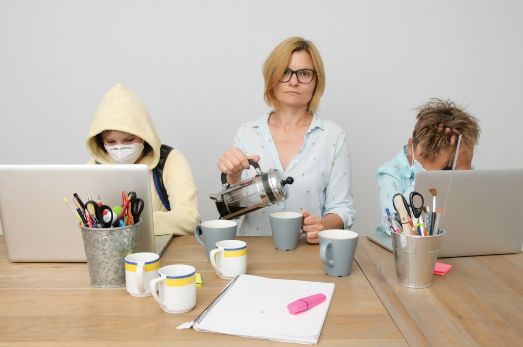 the photo of the situation when mom and kids during the covid time having the home schooling