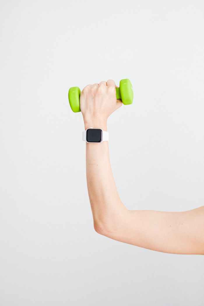 person wearing white apple watch while holding green dumbbell