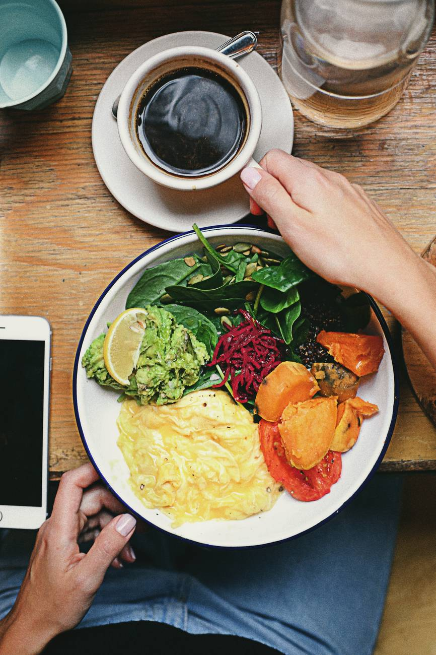 person touching cup of coffee and plate with food