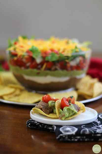 Chips with 7 layer dip on appetizer plate.