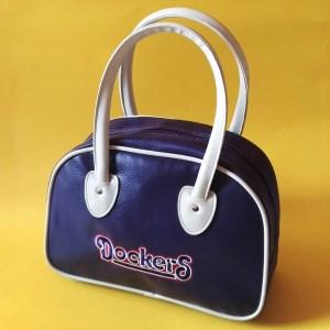 bowling bag dockers, borsa viola su sfondo giallo