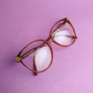 occhiali Roberta di Camerino su sfondo viola, vista dall'alto