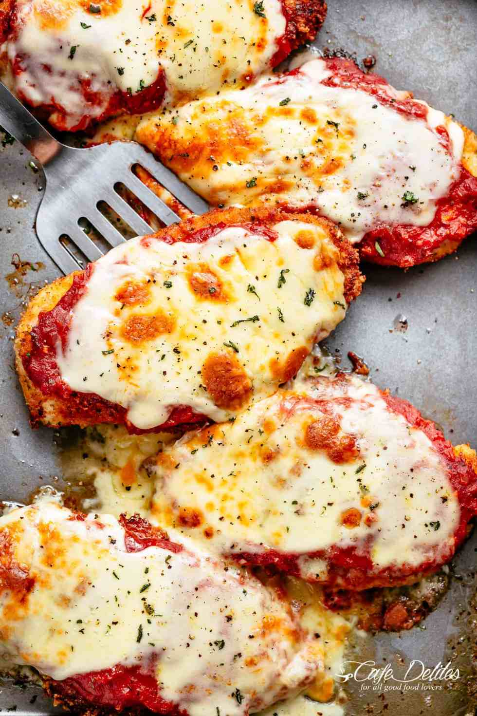 The Best Chicken Parmesan with a deliciously crispy breadcrumb coating, smothered in a rich homemade tomato sauce and melted mozzarella cheese! This is here best Chicken Parmesan you will ever make! Simple to make and worth every minute. If you love a crispy crumb coating vs soggy crumb, look no further! | cafedelites.com