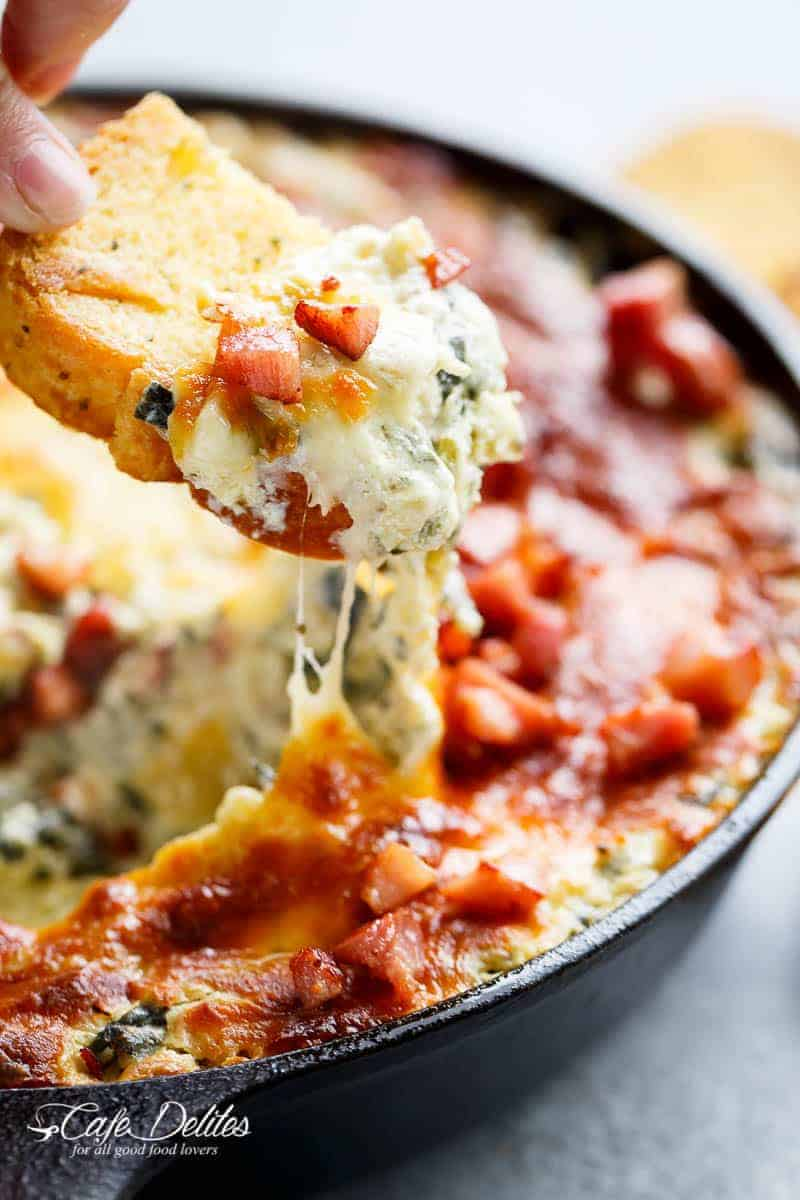 Warm Spinach Bacon Artichoke Dip is a hit around the table! Made with minimal ingredients and topped with crispy bacon, what's not to love! | https://cafedelites.com