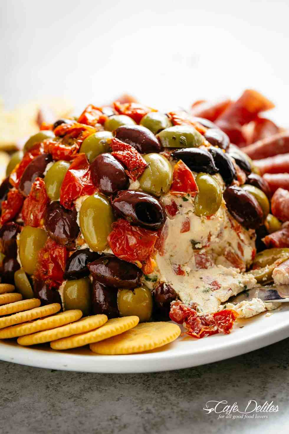 Cheese Ball Antipasto is a perfect centre piece for any occasion! Full of antipasto ingredients on the inside and covered in them on the outside! Serve it on a platter with cold meats such as salami and prosciutto, PLUS crackers! | cafedelites.com