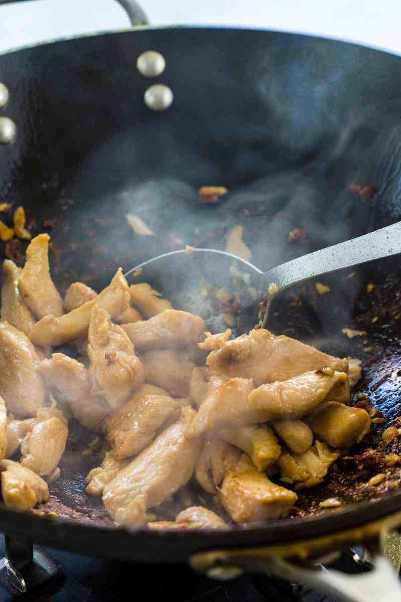 stir frying pieces of chicken in a wok