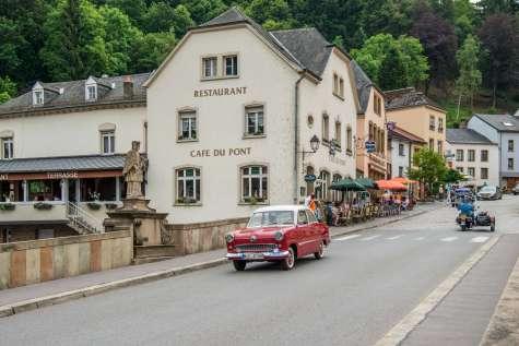 Illustratie: foto vanaf de straat in Vianden waaraan Café Du Pont ligt. Op de foto rijdt een rode oldtimer over de brug.