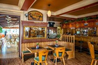 Illustratie: interieurfoto. Op de foto is een deel van de bar te zien en een aantal tafels en stoelen.