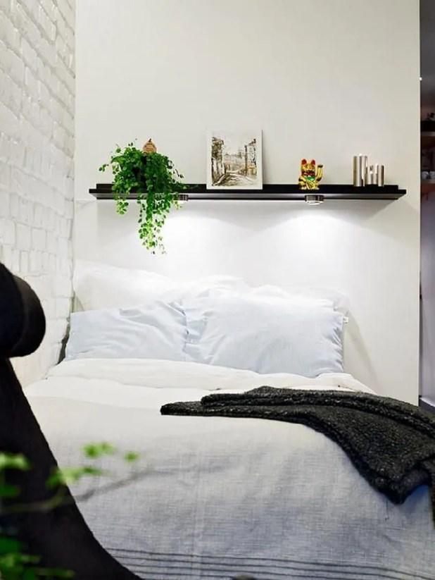 Ngay đối diện là góc nghỉ ngơi được thiết kế vô cùng đơn giản. Một chiếc giường đơn êm ái với kệ đầu giường được trang trí bằng cây xanh, ảnh và những đồ lưu niệm.