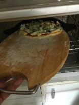 Using the chopping board to slide the pizza in