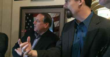 Dave Davidson shows Mike Huckabee the section of the exhibit dedicated to his campaign.