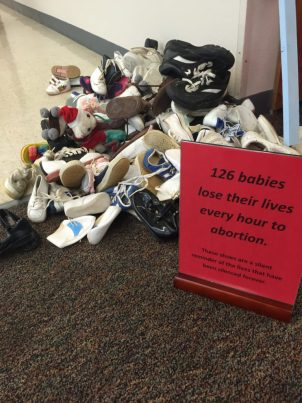 Pile of shoes representing the 126 babies killed every hour in the US.