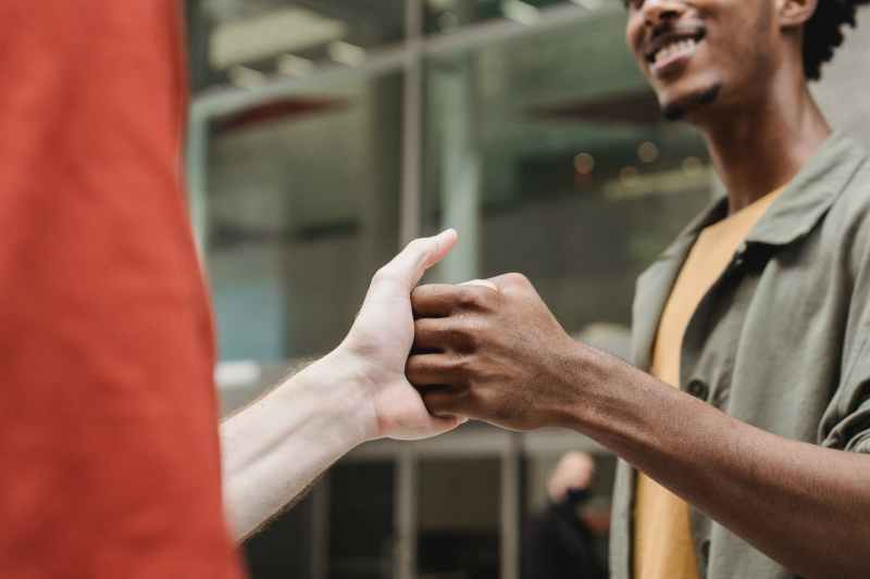 crop positive multiethnic guys shaking hands on street