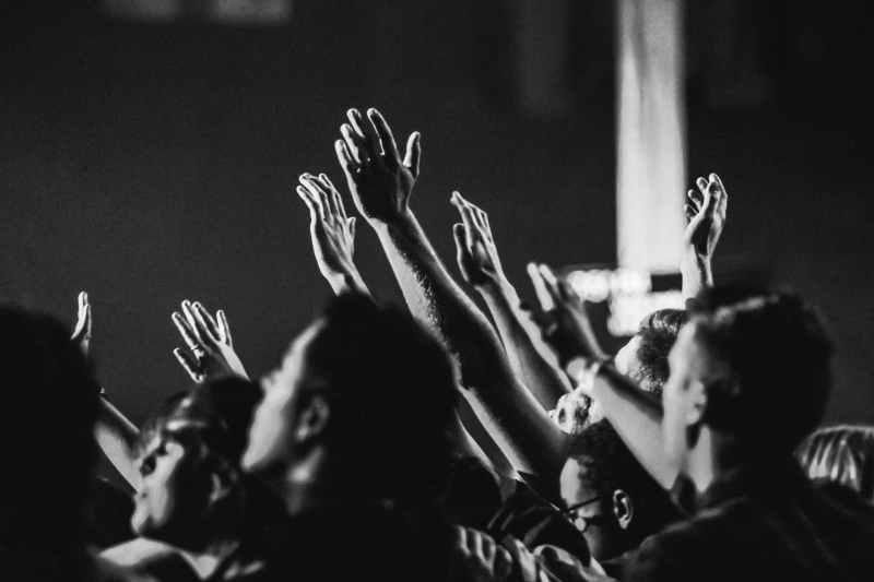 grayscale photo of people raising their hands