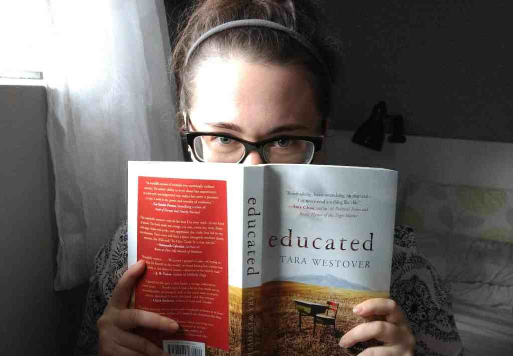 "A photograph of me peaking over a book, ""Educated"" by Tara Westover."