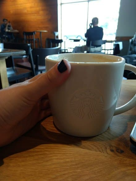 A hand holding a Starbucks mug in a Starbucks cafe.